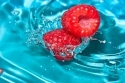 Fresh raspberry on a background of blue water.